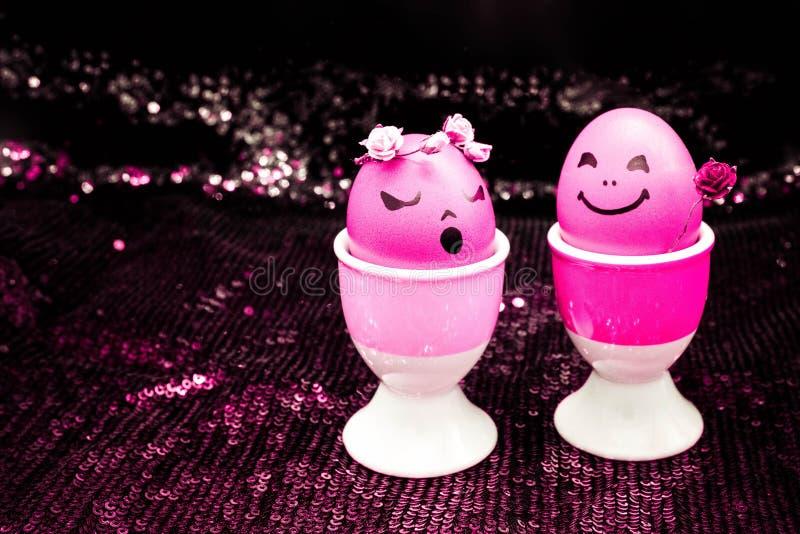 Los huevos rosados felices de pascua con la historieta exhausta pintada hacen frente en fondo brillante negro El muchacho da la f imágenes de archivo libres de regalías