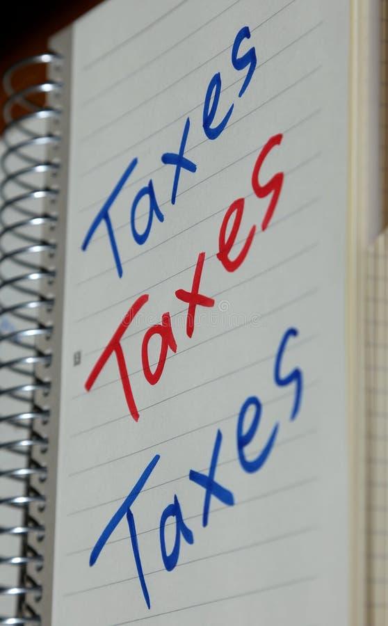 Los impuestos gravan los impuestos escritos sobre el cuaderno de notas fotos de archivo libres de regalías
