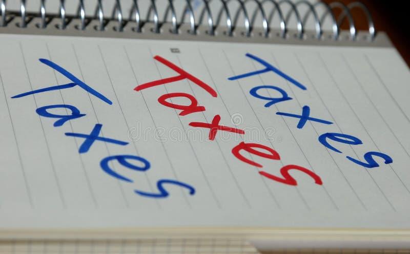 Los impuestos gravan los impuestos escritos sobre el cuaderno de notas imagenes de archivo
