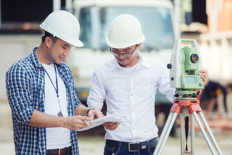 Los ingenieros civiles en el emplazamiento de la obra y A aterrizan al topógrafo que usa a foto de archivo libre de regalías