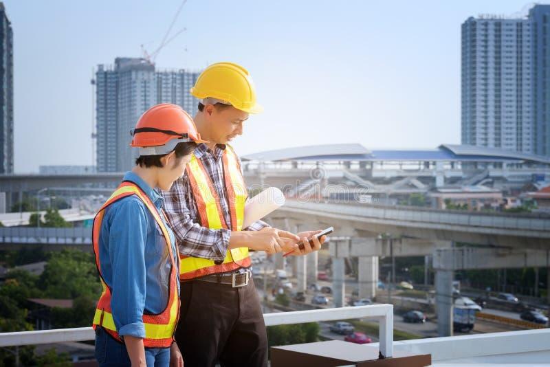 Los ingenieros del hombre se colocan en edificios altos y hablan de los teléfonos celulares fotografía de archivo libre de regalías