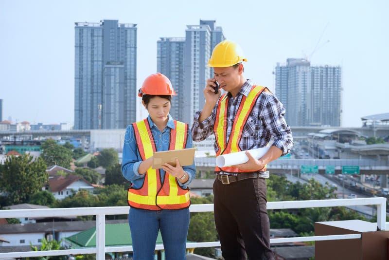Los ingenieros del hombre se colocan en edificios altos y hablan de los teléfonos celulares imagenes de archivo