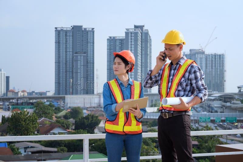 Los ingenieros del hombre se colocan en edificios altos y hablan de los teléfonos celulares foto de archivo