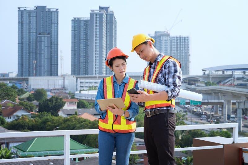 Los ingenieros del hombre se colocan en edificios altos y hablan de los teléfonos celulares foto de archivo libre de regalías