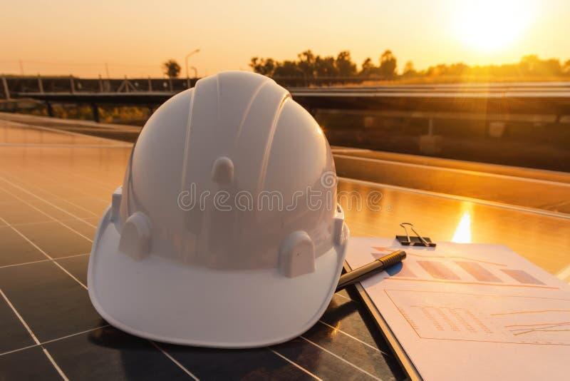 Los ingenieros están examinando las cartas de funcionamiento de la producción energética de los paneles solares que son la energí foto de archivo libre de regalías