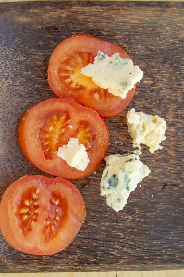 Los ingredientes culinarios italianos cortaron los tomates y el queso con el molde en una placa de madera rústica oscura imagen de archivo