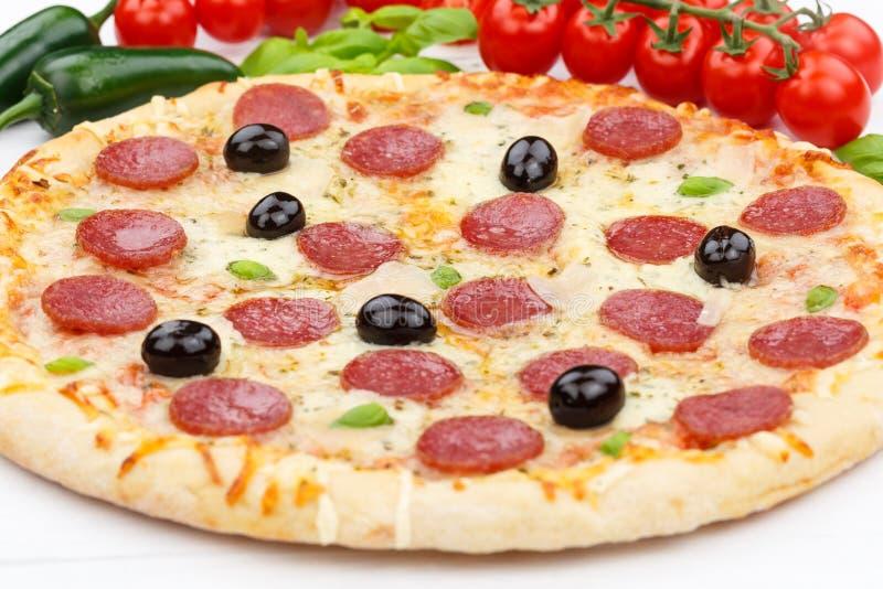 Los ingredientes de la hornada del salami de los salchichones de la pizza se cierran para arriba en el tablero de madera imagen de archivo