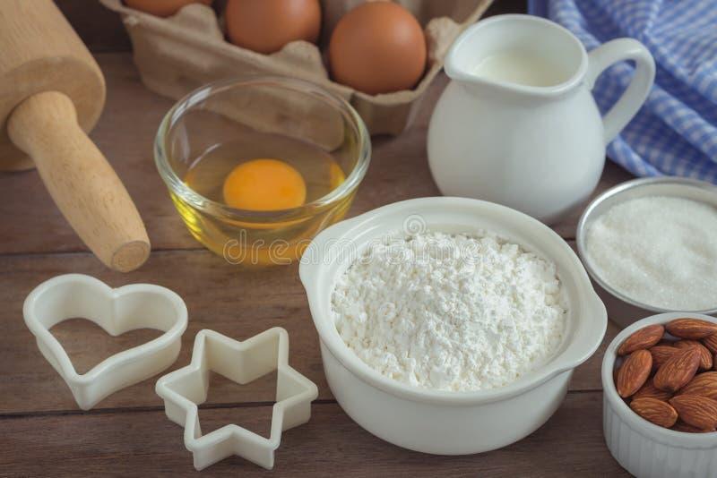 Los ingredientes de la hornada flour, egg, ordeñan, las almendras, azúcar en TA de madera imagen de archivo libre de regalías
