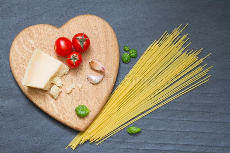 Los ingredientes de las pastas de los espaguetis resumen la comida en fondo negro imagenes de archivo