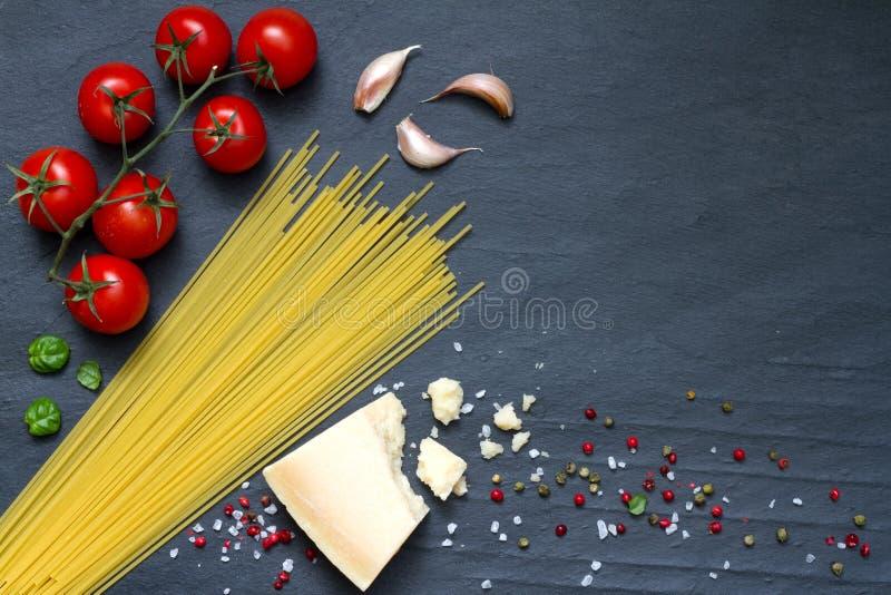 Los ingredientes de las pastas de los espaguetis resumen la comida en fondo negro fotografía de archivo libre de regalías