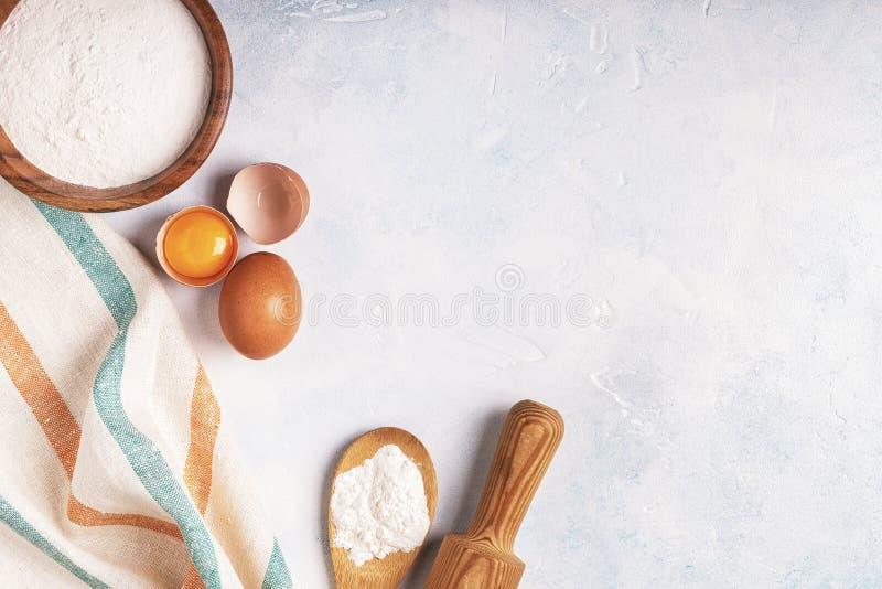 Los ingredientes para cocer - flour, cuchara de madera, huevos imagenes de archivo
