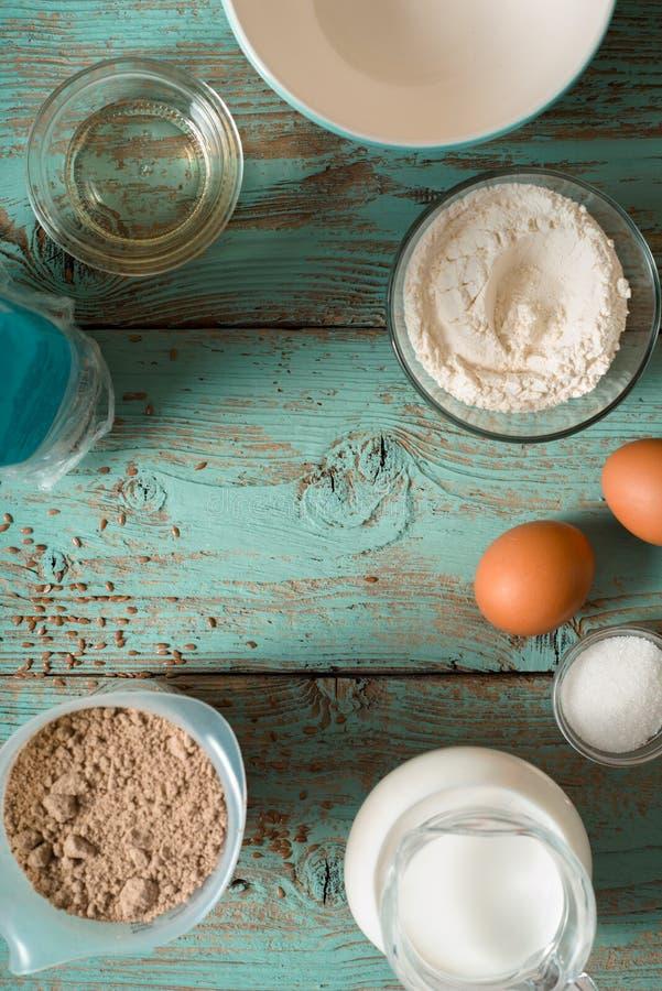 Los ingredientes para el gluten de las crepes liberan en la tabla de madera azul imágenes de archivo libres de regalías
