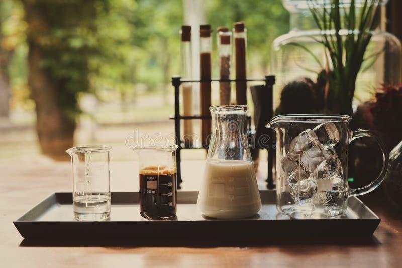 Los ingredientes para hacer el latte fr?o del caf?, la leche del caf? express de los cubos de hielo y el jarabe dulce sirvieron e foto de archivo libre de regalías