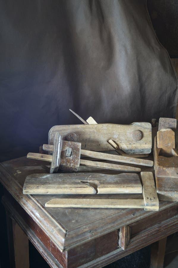 Los instrumentos del viejo carpintero a descansar sobre la tabla de madera fotografía de archivo