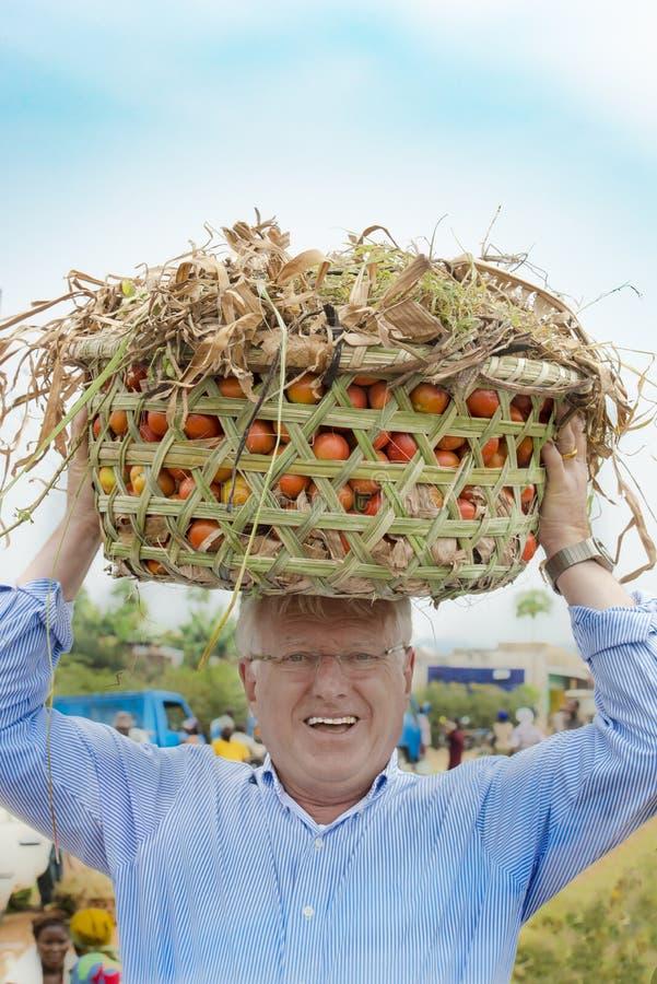 Los intentos europeos del hombre para llevar la cesta del tomate en la cabeza como mujeres africanas hacen foto de archivo libre de regalías