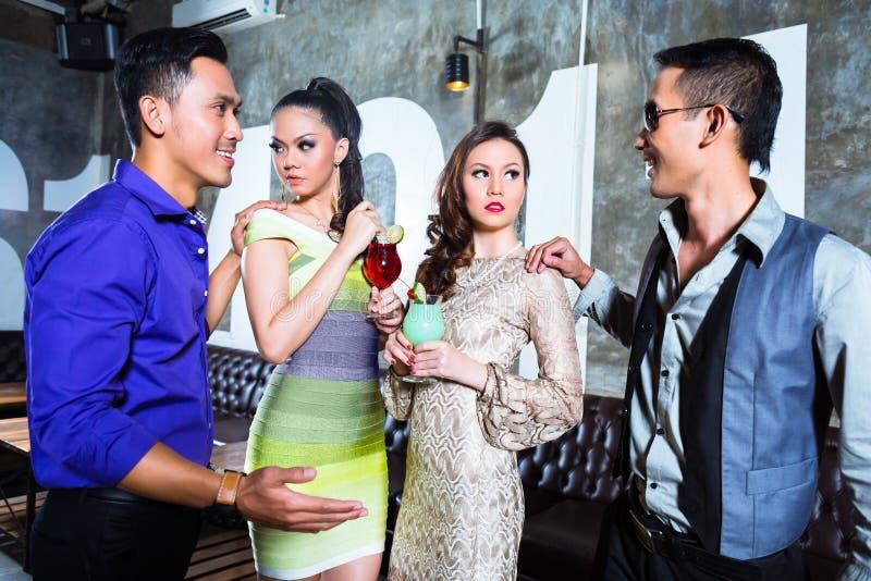 Los jóvenes asiáticos van de fiesta los pares que beben los cócteles en club foto de archivo