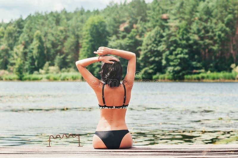 Los jóvenes broncean a la mujer en bikini por el lago fotografía de archivo libre de regalías