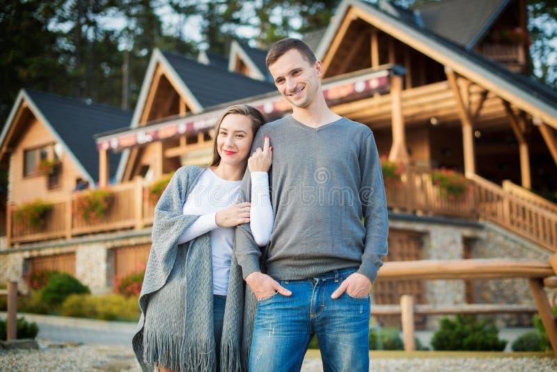 Los jóvenes casados juntan derecho fuera de su cabaña de madera grande en el bosque imagenes de archivo