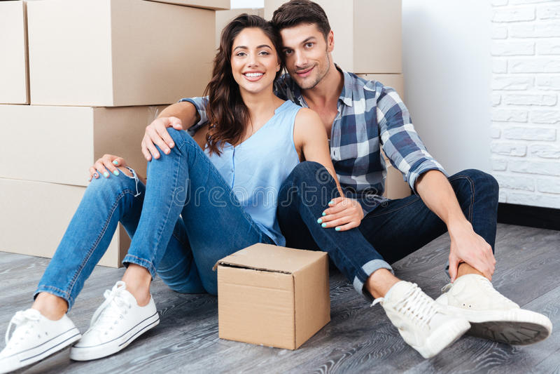 Los jóvenes casados juntan sentarse en su nueva casa fotografía de archivo libre de regalías