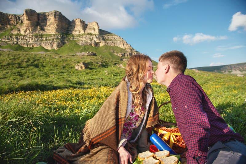 Los jóvenes casados se juntan en comida campestre al aire libre imagenes de archivo