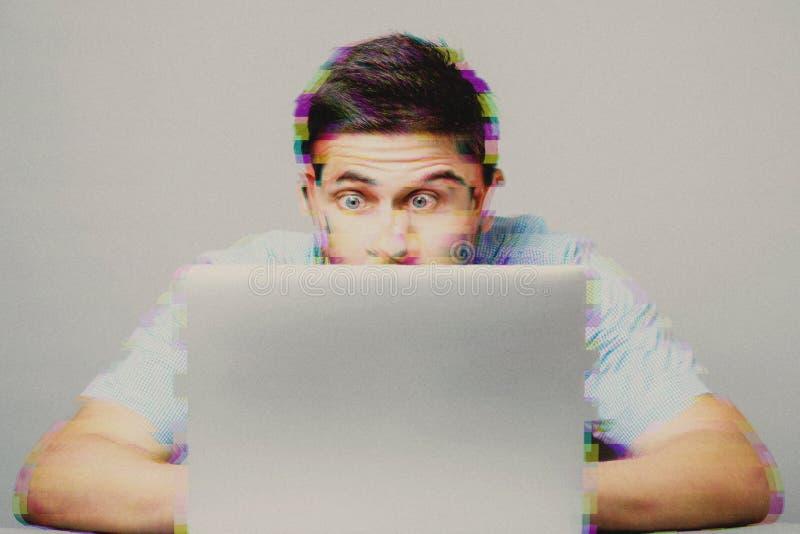 Los jóvenes chocaron al hombre en camisa azul usando el ordenador portátil fotografía de archivo
