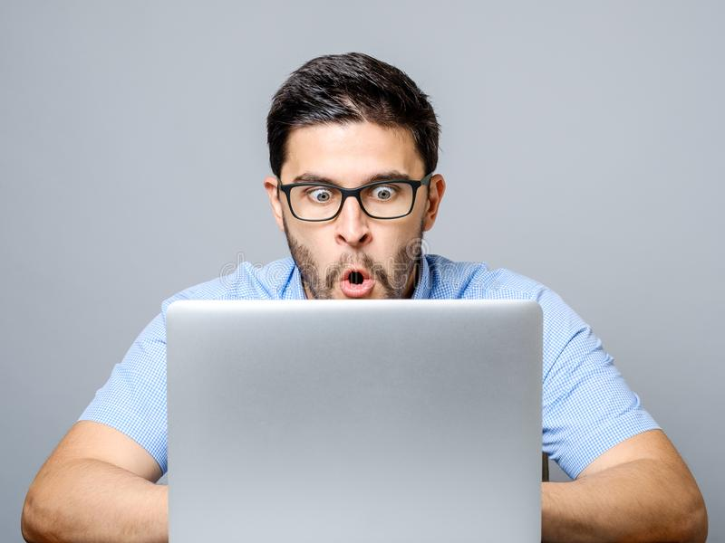Los jóvenes chocaron al hombre en camisa azul usando el ordenador portátil imagen de archivo