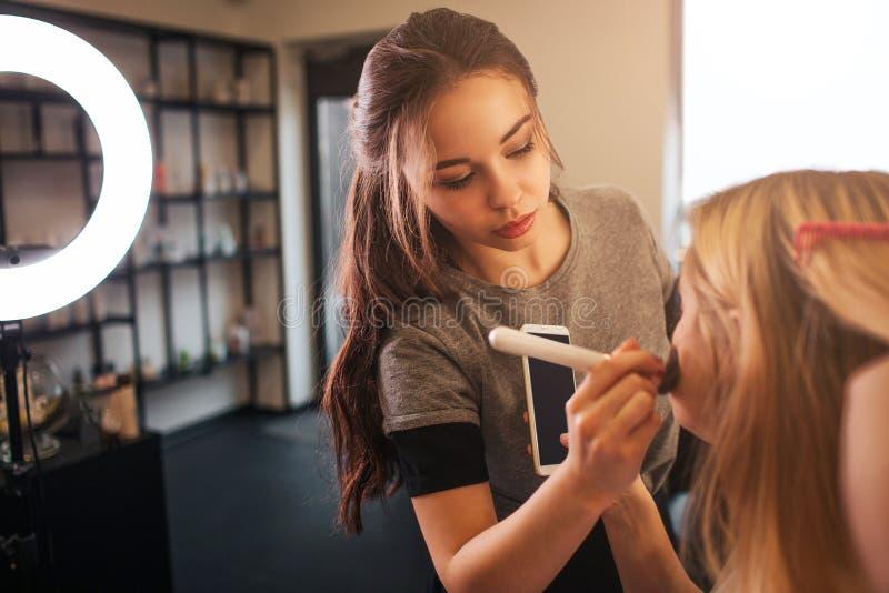 Los jóvenes componen al artista que la aplicación se ruboriza en mejillas rubias de la mujer en sitio de la belleza Mirada profes imagen de archivo libre de regalías