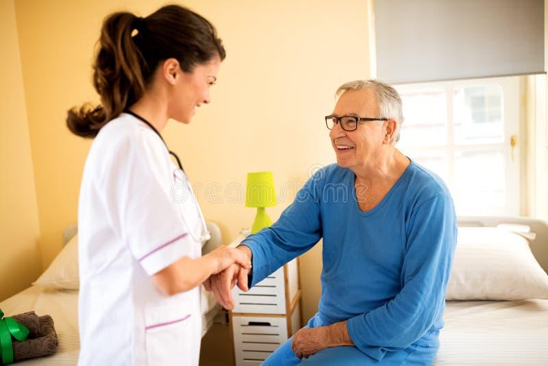 Los jóvenes cuidadosos cuidan al paciente mayor de las ayudas para levantarse fotos de archivo libres de regalías