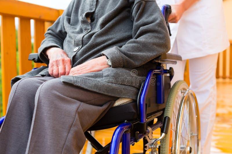 Los jóvenes cuidan y mayor femenino en una silla de rueda imagenes de archivo