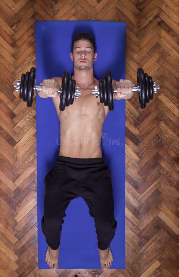 Los jóvenes cupieron al hombre fuerte que ejercitaba pesos de los músculos de la pesa de gimnasia del pecho imagenes de archivo