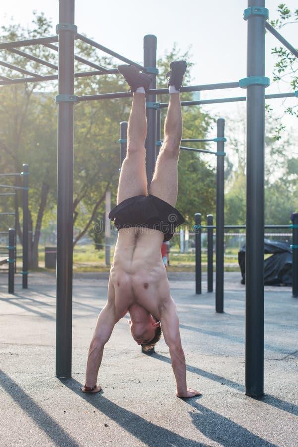 Los jóvenes cupieron al hombre muscular que hacía entrenamiento de la posición del pino al aire libre fotografía de archivo