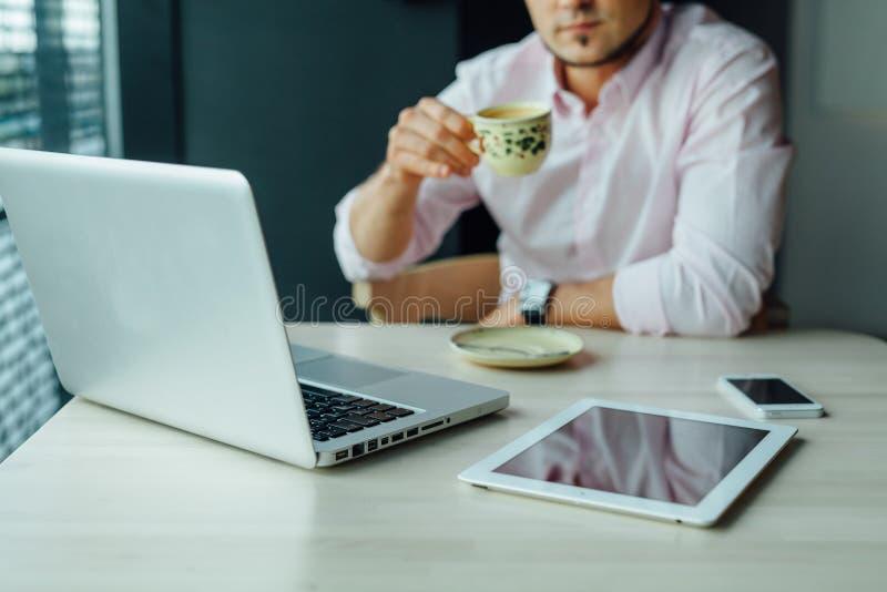 Los jóvenes enfocaron al hombre de negocios que se sentaba en café con el ordenador portátil, tableta p foto de archivo