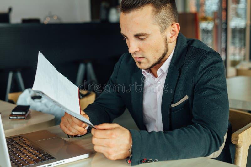 Los jóvenes enfocaron al hombre de negocios que se sentaba en café con el ordenador portátil y analy fotografía de archivo