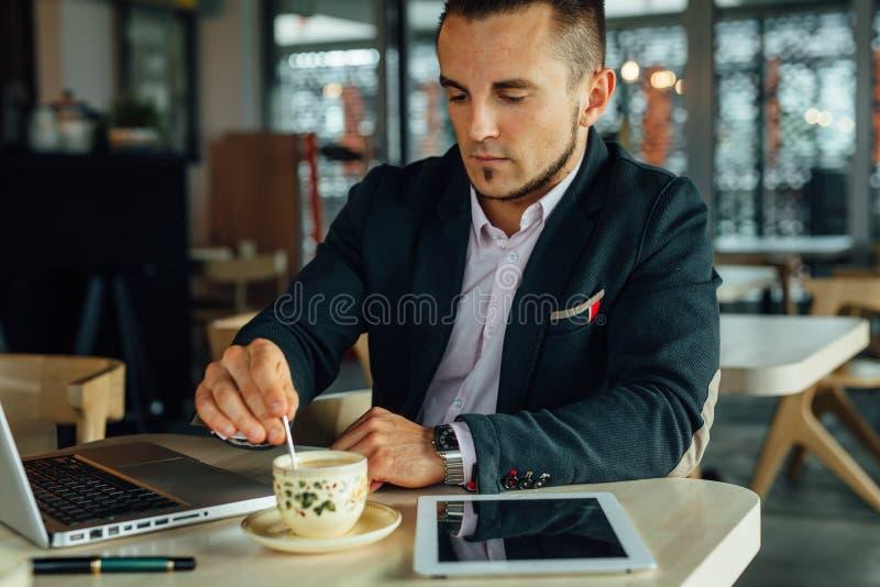 Los jóvenes enfocaron al hombre de negocios que se sentaba en café con el ordenador portátil y el stirr imagen de archivo