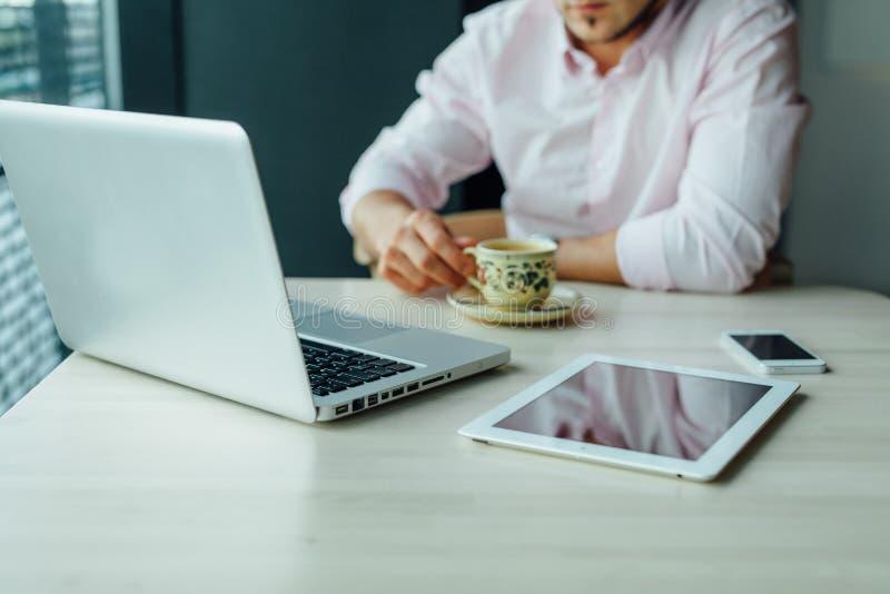 Los jóvenes enfocaron al hombre de negocios que se sentaba en café con el ordenador portátil, PC de la tableta fotos de archivo