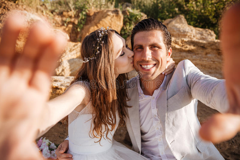 Los jóvenes felices casados juntan la fabricación del selfie en la playa fotografía de archivo libre de regalías