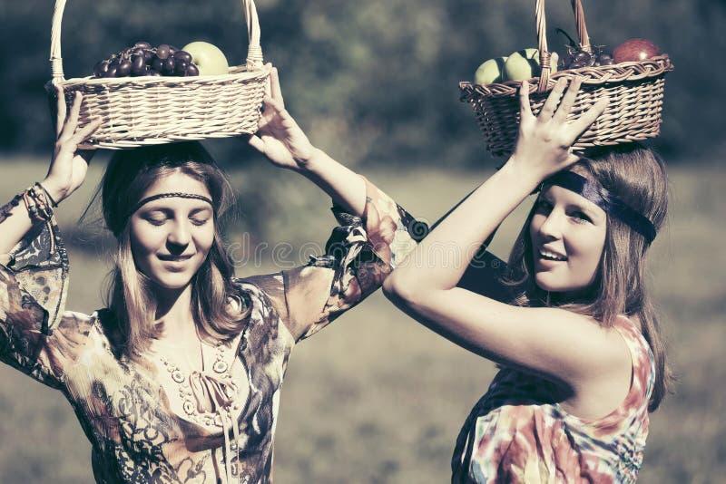 Los jóvenes felices forman a las muchachas con una cesta de fruta que caminan en prado del verano fotos de archivo