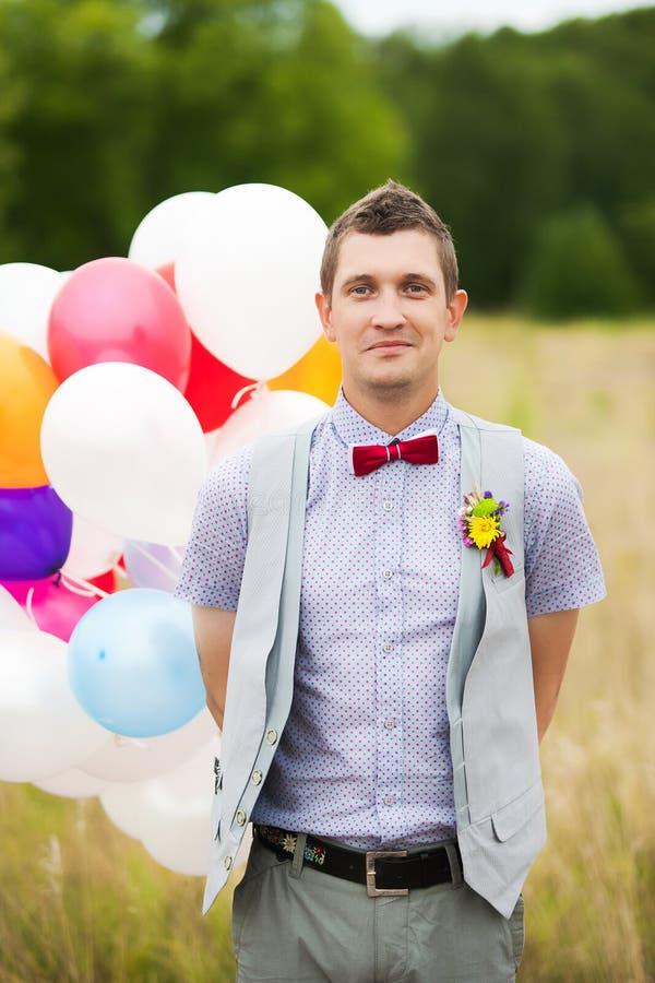 Los jóvenes felices preparan sostenerse en globos coloridos del látex de las manos imágenes de archivo libres de regalías