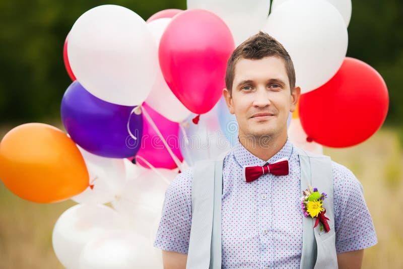 Los jóvenes felices preparan sostenerse en globos coloridos del látex de las manos imagen de archivo