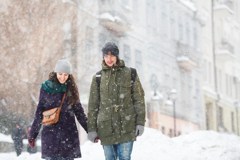 Los jóvenes felices se juntan en la ciudad del invierno que se divierte fotos de archivo libres de regalías