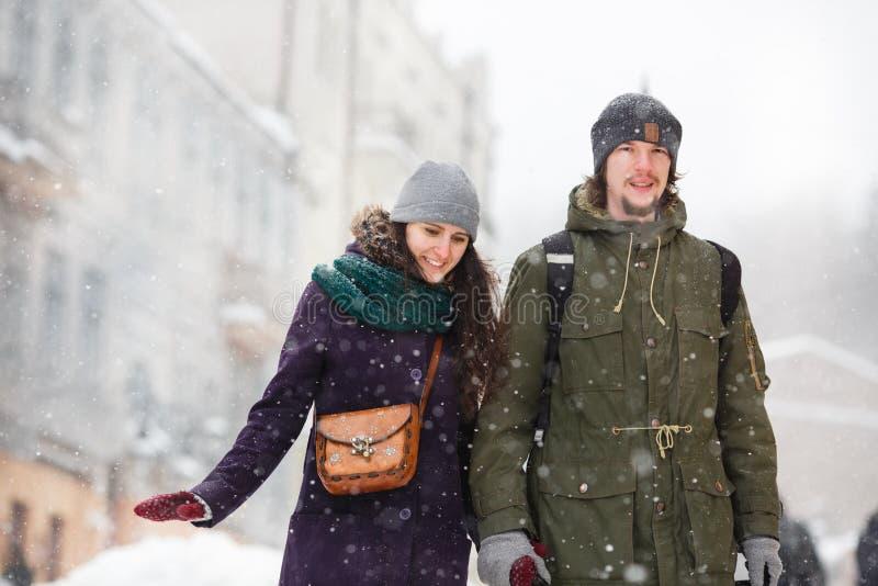 Los jóvenes felices se juntan en la ciudad del invierno que se divierte foto de archivo