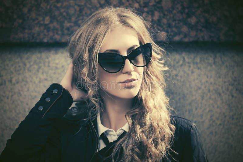 Los jóvenes forman a la mujer de negocios rubia en gafas de sol en la calle de la ciudad fotos de archivo libres de regalías