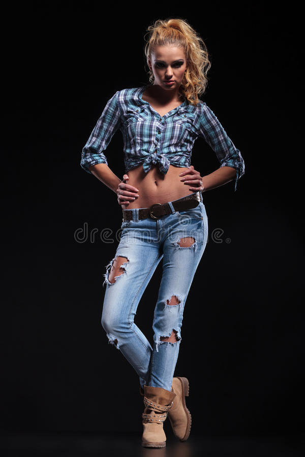 Los jóvenes forman a la mujer rubia con las manos en caderas foto de archivo