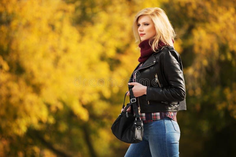 Los jóvenes forman a la mujer rubia en la chaqueta de cuero en parque del otoño fotos de archivo