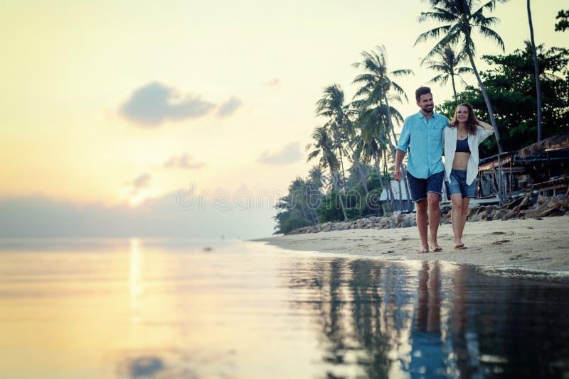 Los jóvenes hermosos aman el brazo que camina de los pares felices en brazo en la playa en la puesta del sol durante el viaje de  fotografía de archivo libre de regalías