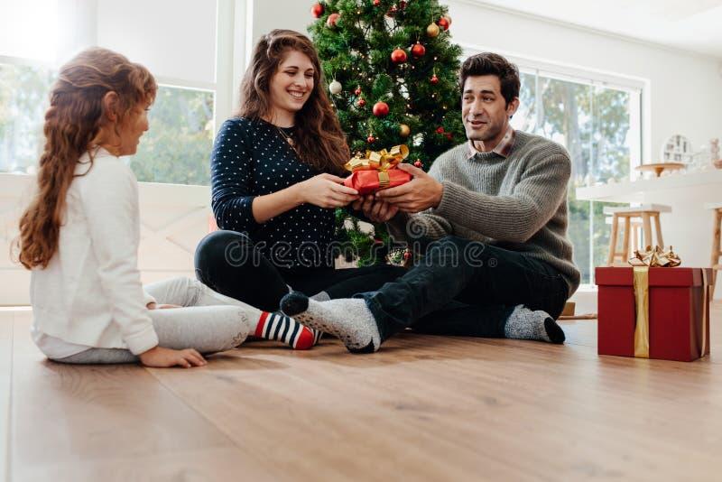 Los jóvenes juntan la celebración de la Navidad con su hija fotos de archivo