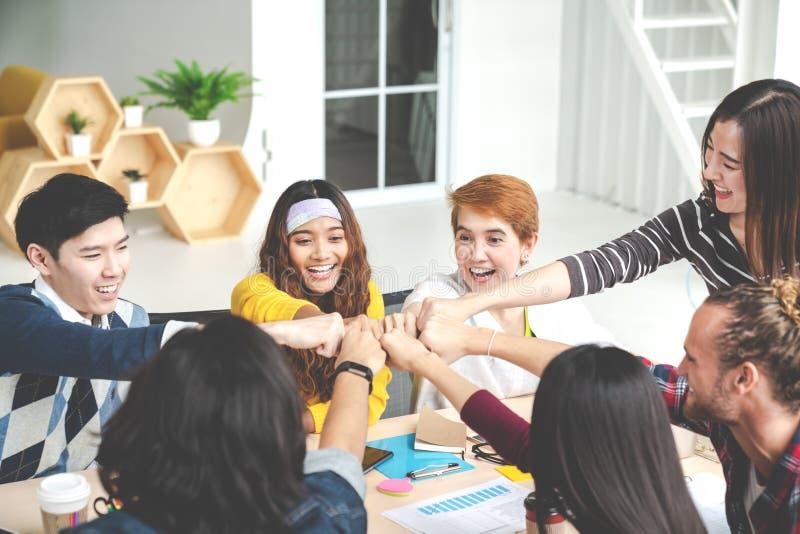 Los jóvenes multiétnicos combinan las manos de la pila juntas como la unidad y trabajo en equipo en oficina moderna Colaboración  foto de archivo libre de regalías
