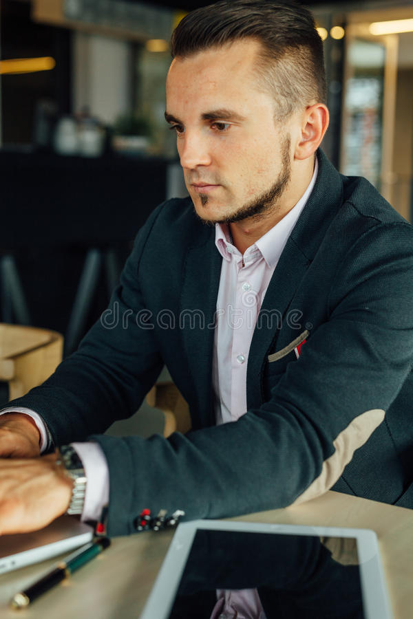 Los jóvenes se centraron al hombre de negocios que se sentaba en café y que trabajaba en su la fotos de archivo libres de regalías