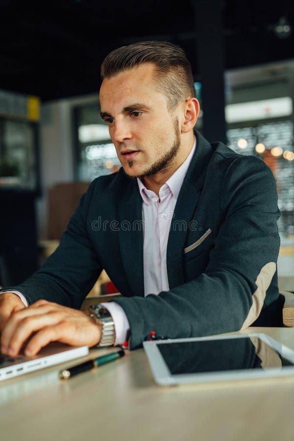 Los jóvenes se centraron al hombre de negocios que se sentaba en café y que trabajaba en su la imagen de archivo libre de regalías