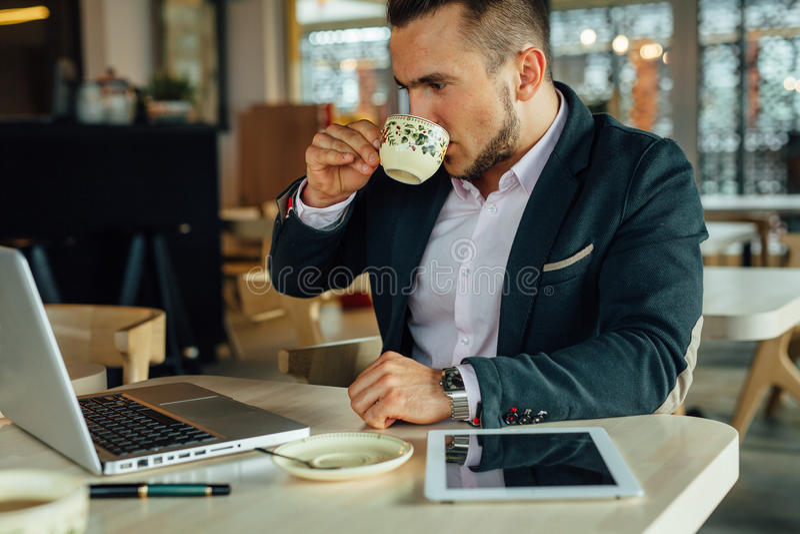 Los jóvenes se centraron al hombre de negocios que se sentaba en el café, trabajando en su lapto fotos de archivo